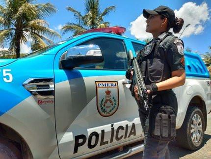 Policial militar em frente à uma viatura