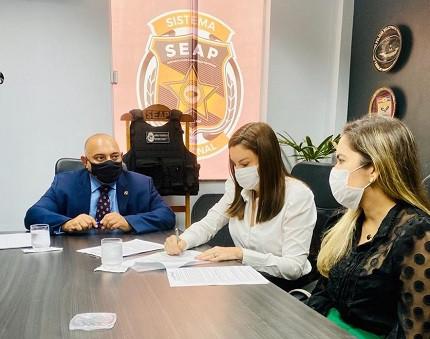 Secretária Hana Ghassan (ao centro) durante a assinatura do contrato com o Cetap para organizar o concurso Seap PA