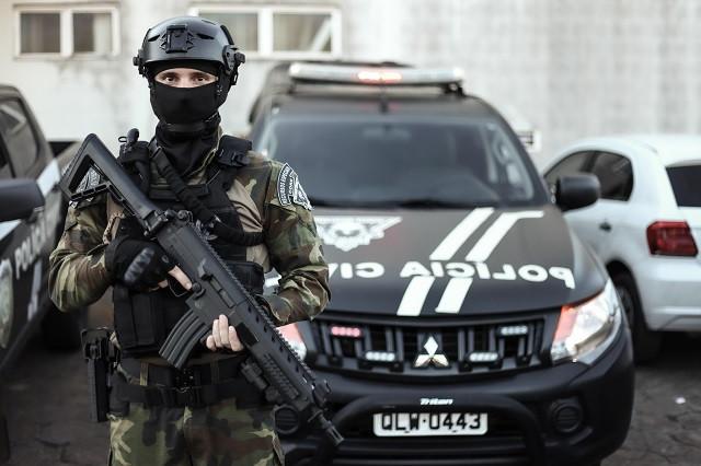 Policial civil do Acre armado na frente de uma viatura